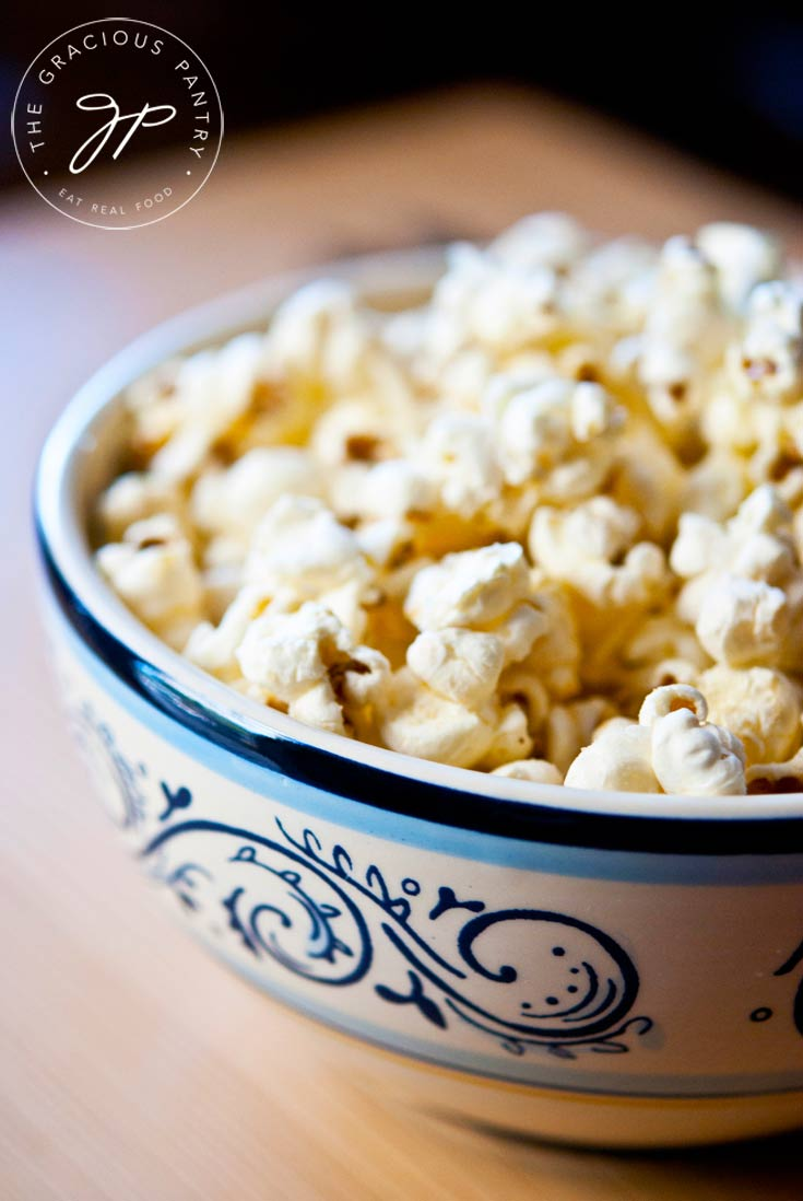 A blue and white bowl of Clean Eating Garlic Parmesan Popcorn sits on a wooden table with a black background.