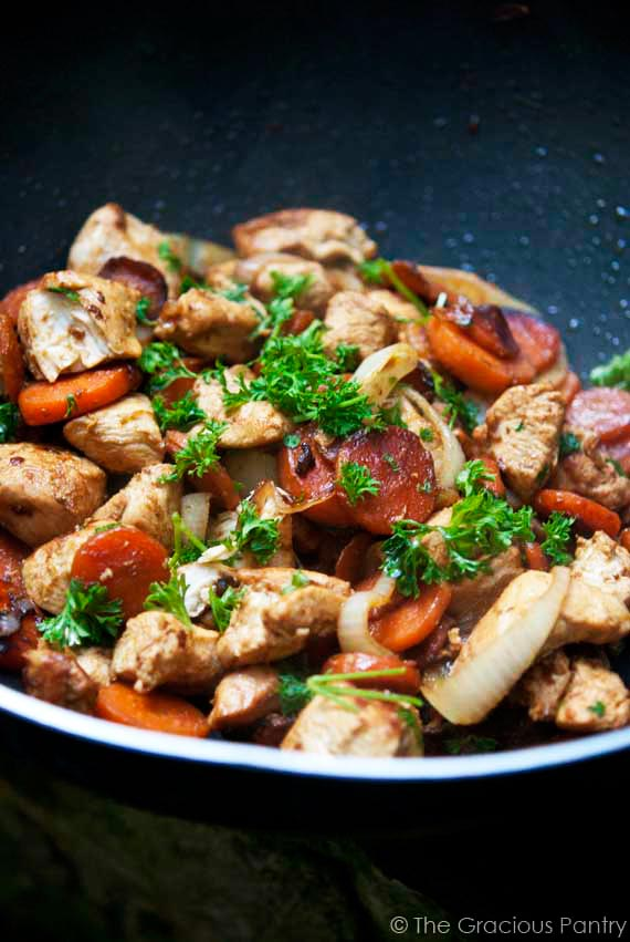 Clean Eating Wok-Style Garlic Chicken & Carrots recipe sitting in a black skillet with vibrant orange carrots and delicious looking chicken, sprinkled with fresh parsley for garnish.