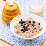 A bowl of this Almond Porridge sits next to a yellow honey pot and a small container of milk.