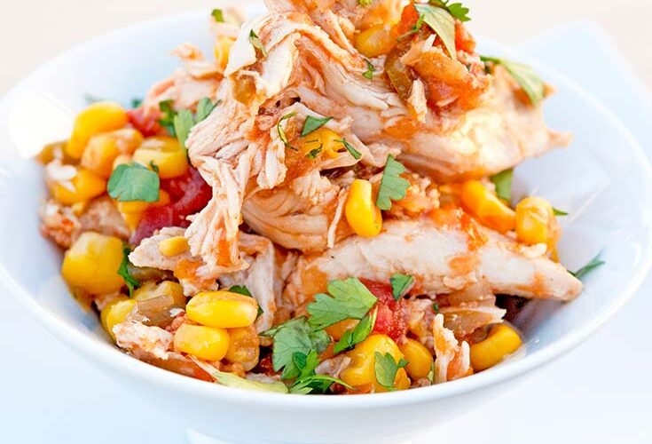 A full bowl of this Sweet And Spicy Crock Pot Chicken sits on a table, ready to eat.