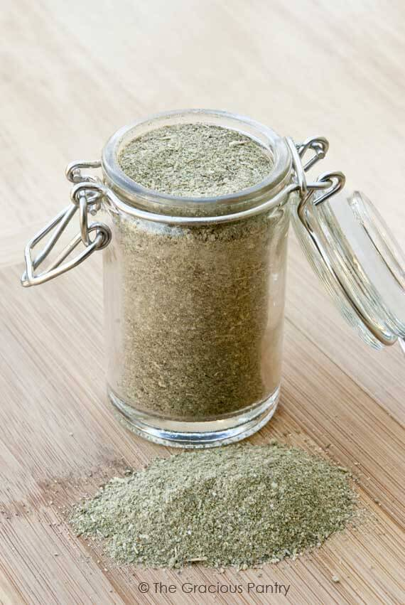 Clean Eating Italian Seasoning in a clear glass jar with the attached lid open, showing all the dry spices in the jar.