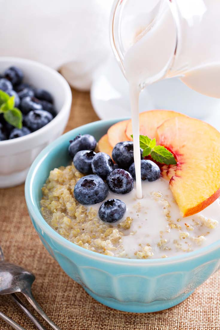 A bowl sits filled with breakfast quinoa and has blueberries and peach slices on it. A bit of milk is being poured on from a white pitcher.