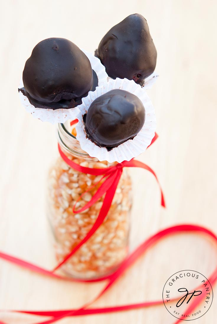 A jar filled with dry popcorn kernels holds three Clean Eating Chocolate Covered Strawberries on sticks. A red ribbon is tied around the jar and the ribbon falls nicely around the jar on the table.