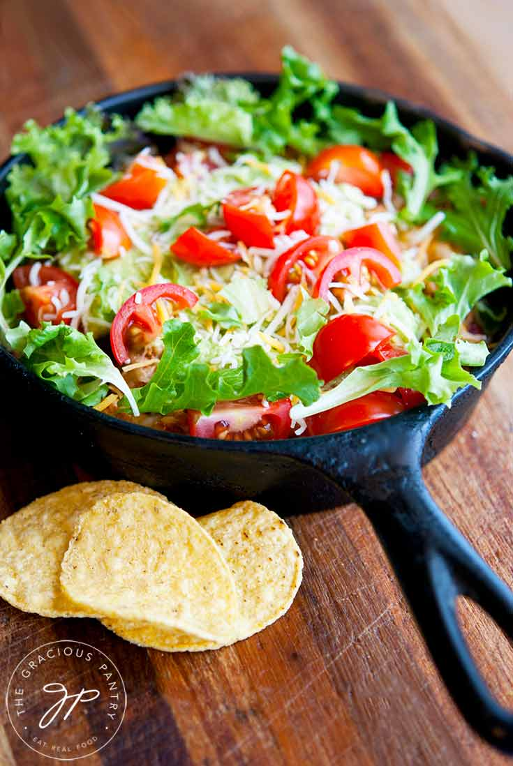 A small, cast iron skillet sits on a wood surface, filled with this Clean Eating Skillet Taco Salad. You can see beautiful, bright green lettuce and fresh-cut, red cherry tomatoes with shredded cheese sprinkled over the top. A few corn chips sit to the side.