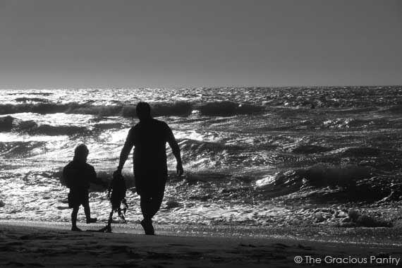 Black and white mage of a father and sun, walking on the beach represents this post on a Clean Eating Fathers Day Menu