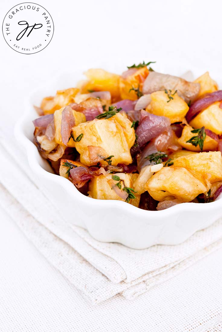 A bowl of Roasted Sweet Potato Salad sits on a table, ready to serve.