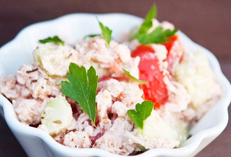 A white bowl filled with this Chicken And Cucumber Salad sits garnished with parsley and ready to eat.