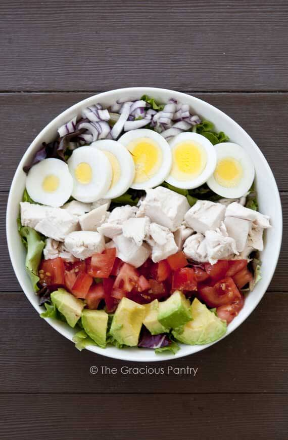 A Clean Eating Cobb Salad in a white bowl on a dark wood background. The salad is shown from over head, looking down into the bowl. The salad is unmixed so you can see each of the ingredients arranged nicely on top of the lettuce.
