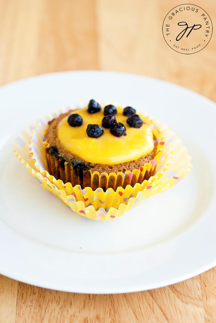 A single cupcake from a batch of these Clean Eating Blueberry Cupcakes with Lemon Curd Frosting sits on a small, white plate. The cupcake paper is pulled away from the cupcake and the lemon curd frosting on top of the cupcake is topped with blueberries.