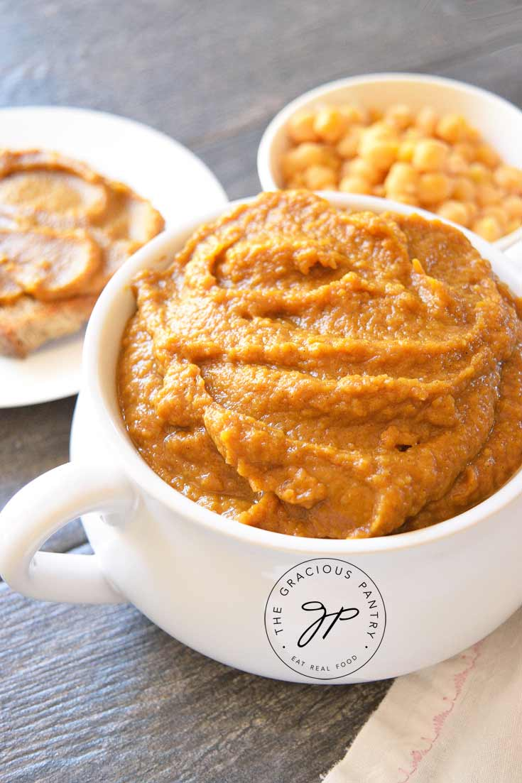 A bowl of this Clean Eating Pumpkin Hummus sits next to a small plate with a piece of toast. The toast has been slathered in pumpkin hummus. There is also a small bowl os chickpeas standing off to the side.