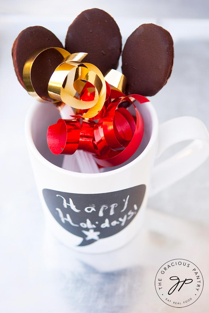 Three Clean Eating Chocolate Covered Spoons are held in a white mug with the chocolate end up. Colorful gold and red ribbon has been tied around them for a festive look.
