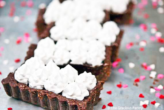 Clean eating margarita chocolate truffle tart makes a rich, chocolatey dessert for a clean eating Valentine's Day. Served cut, with whipped cream pipped onto the top.