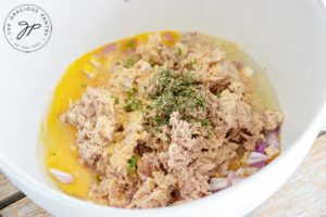 Ingredients for these clean eating tuna patties put together in a mixing bowl, ready to mix for forming the patties.
