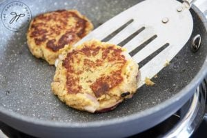 Two clean eating tuna patties cooking in a skillet as one gets flipped over with a metal spatula.