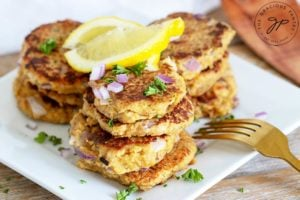 Freshly cooked, clean eating tuna patties sit on a plate with a lemon wedge, ready to eat.