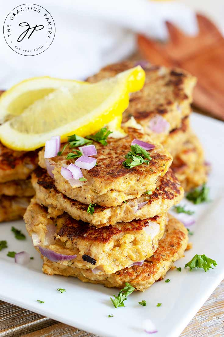A stack of theseClean Eating Tuna Patties sits on a white plate topped with fresh herbs, chopped red onion and some bright yellow lemon wedges.