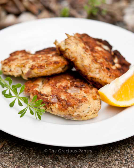 Clean Eating Tuna Patties Recipe on a white plate with lemon wedges and green garnish.