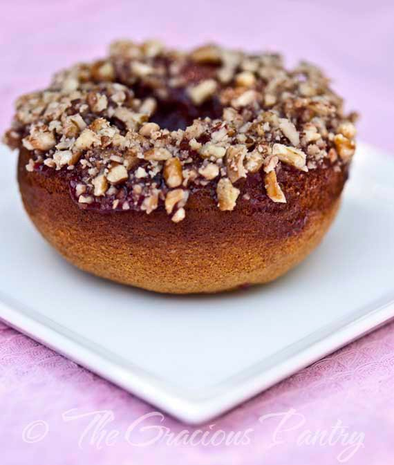A single doughnut from this Clean Eating Doughnuts Recipe sits on a white, square plate. It's shown from the side. You can see the brown doughnut, the layer of fruit topping and the ground nuts sprinkled over the top.