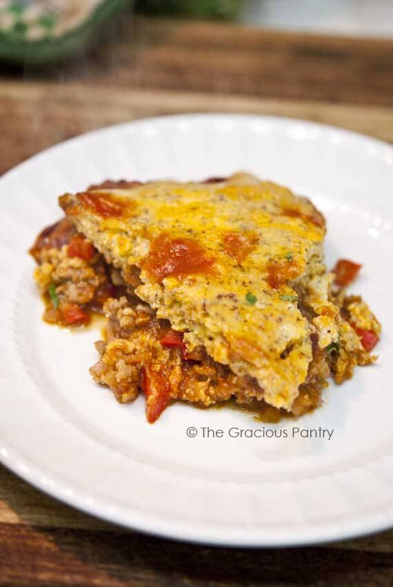 Clean Eating Sloppy Joe Casserole cut and served on a white plate. The bread-like topping sits on top of the ground meat.