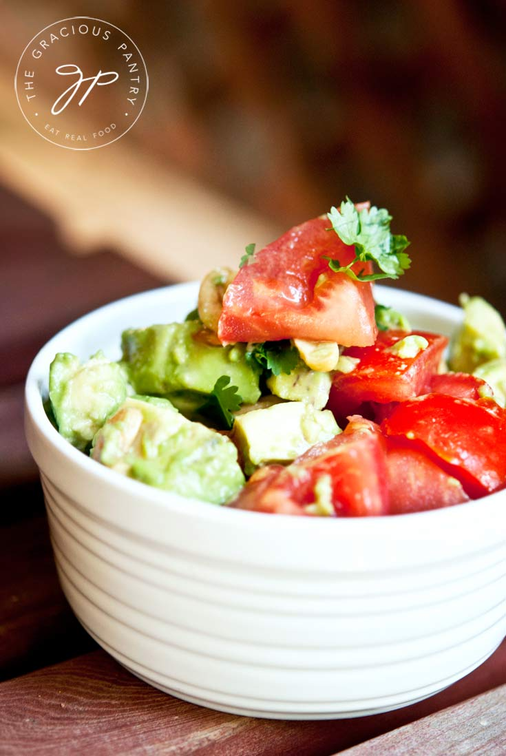 A close up view of a white bowl filled with this Clean Eating Avocado Cashew Salad. You can see chunks of avocado and tomatoes over the top of the bowl.