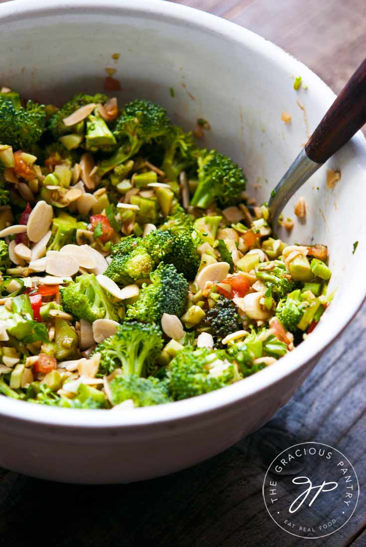 A large white bowl sits filled half way with this Clean Eating Broccoli Salad. Salad spoons are in the bowl as well for serving. You an see tons of broccoli, lots of sliced almonds and a few hints of chopped tomato.