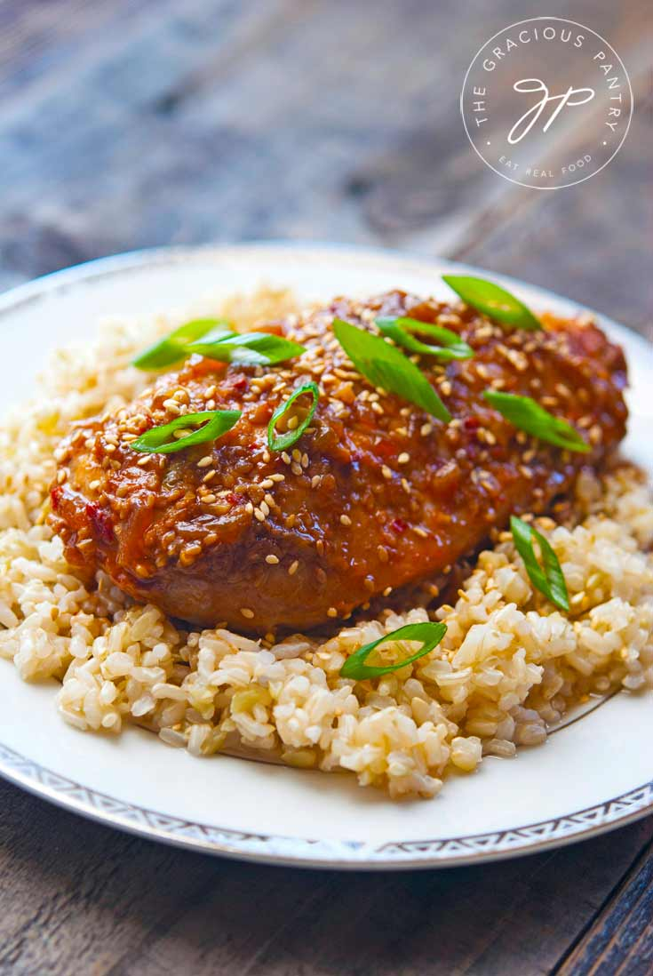 Clean Eating Slow Cooker Honey Sesame Chicken Recipe showing the glazed chicken sitting on a bed of brown rice with sliced green onions lightly sprinkled on top.