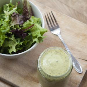 mason jar of avocado lime ranch dressing next to garden salad