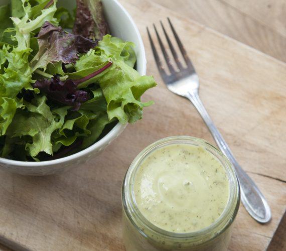 mason jar of avocado lime ranch dressing next to garden salad