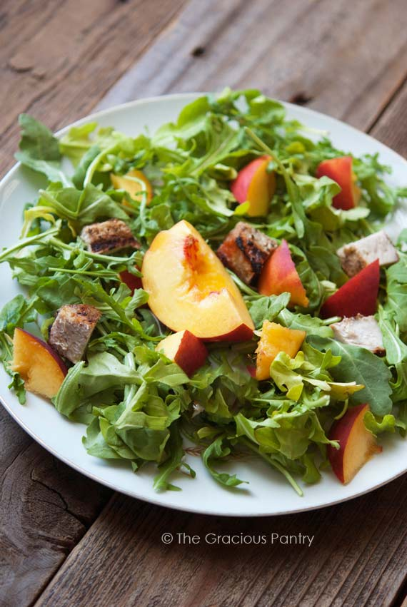 Clean Eating Pork Peach Arugula Salad With Peach Vinaigrette With Peach Vinaigrette sits on a white, round plate, ready to eat. The peaches and pieces of pork sit on a large bed of green arugula.