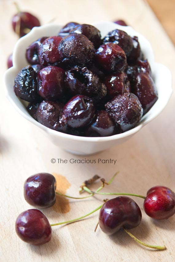 Clean Eating Barbecued Fresh Cherries sitting in a white bowl with fresh, uncooked cherries laying around the base of the bowl.