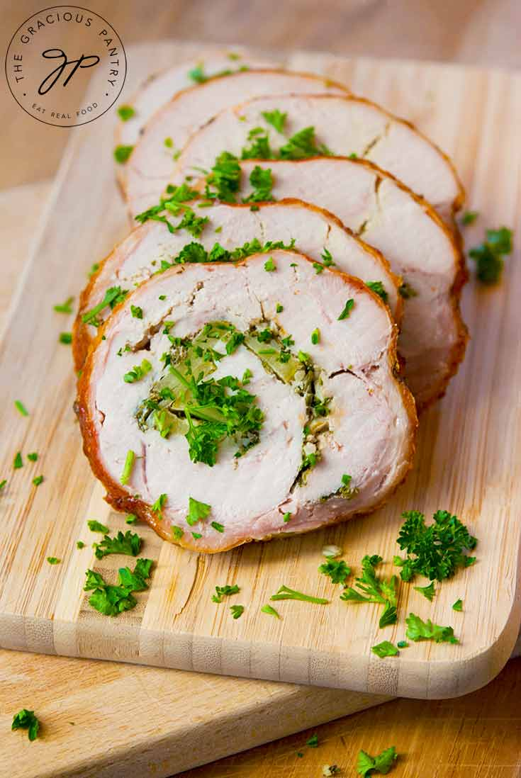 A sliced turkey roulade sits on a cutting board with the slices nicely arranges one on top of the other. They are sprinkled with fresh herbs.