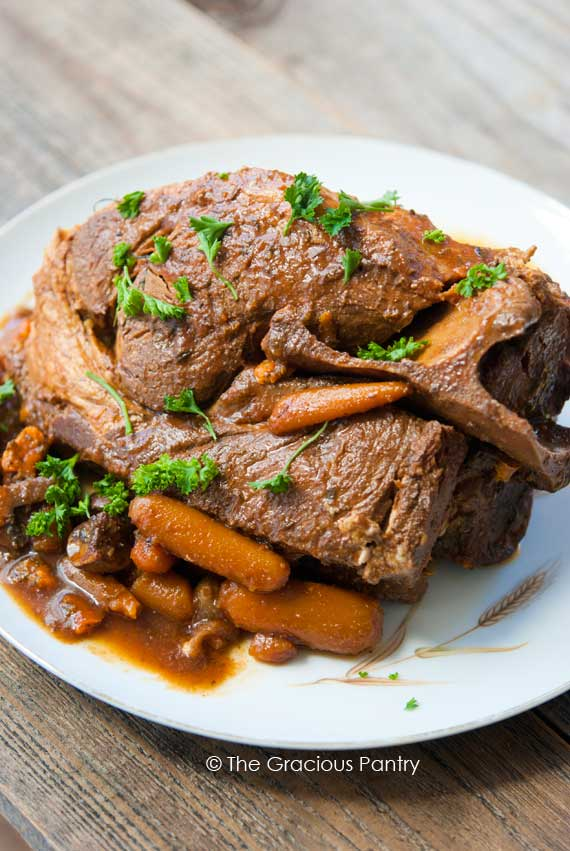 10 Hour Slow Cooker Clean Eating Pork Roast on a platter with some carrots and gravy around the roast with some chopped, green herbs sprinkled over the top for garnish.