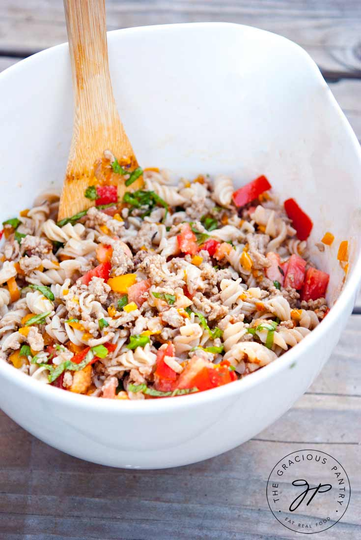 A large, white serving bowl sits filled with this Clean Eating Turkey Vegetable Pasta Salad. A wooden spoon rests on the side of the bowl. The pasta is colorful with all the flecks of brightly colored vegetable tossed about in the bowl.