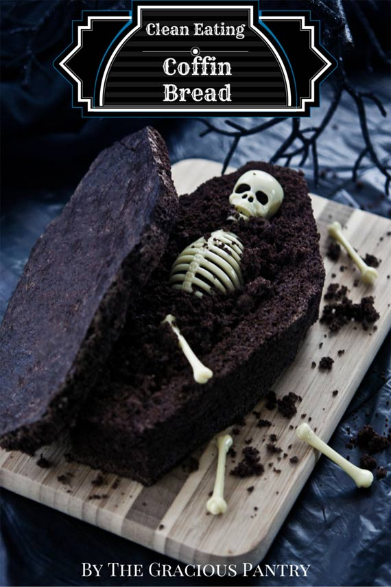 Clean Eating Grain Free Chocolate Coffin Bread Coffin displayed on a dark background. It's been sliced open like a lid on a coffin resting to the side and there is a small, plastic skeleton sitting inside it.