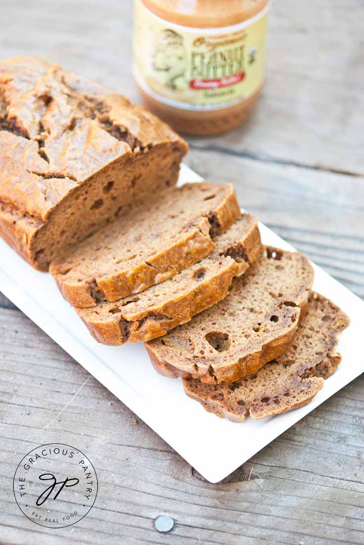 A loaf of Clean Eating Peanut Butter Bread sits partially sliced on a white platter with a jar of peanut butter sitting behind it.