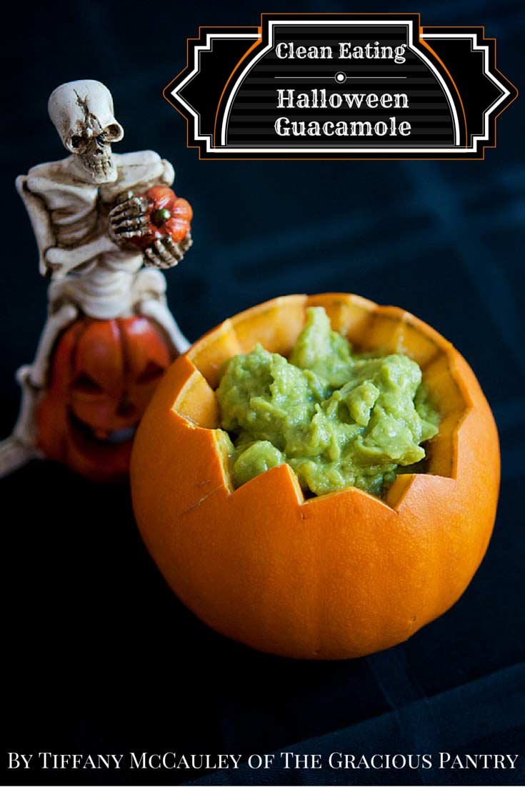 Clean Eating Halloween Guacamole in a pumpkin bowl with a ceramic skeleton sitting next to it.