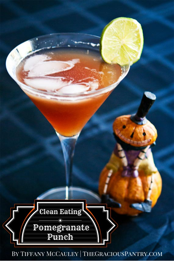 A martini glass filled with Clean Eating Pomegranate Punch has a lime slice on the side and ice floating on top. There is a small, halloween pumpkin statue next to the glass.