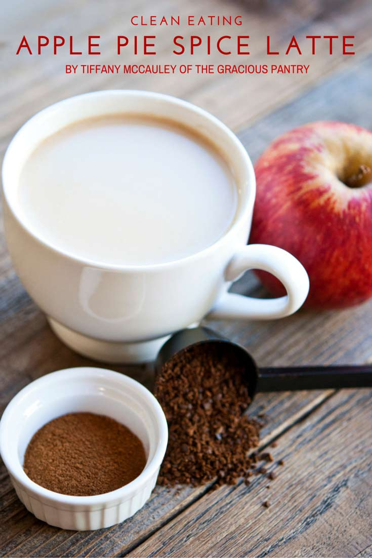 a white mug filled with Clean Eating Apple Pie Spice Latte sits on a wooden table. Next to the mug is an apple, a coffee scoop and a small white dish with coffee grounds.