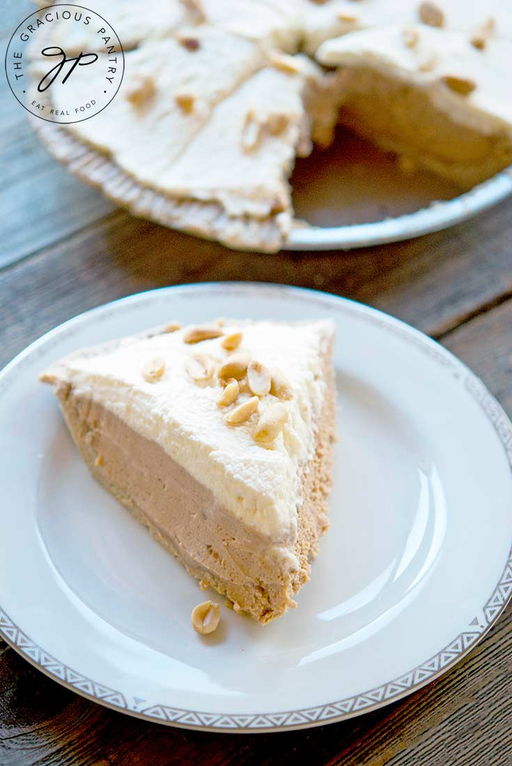 A slice of this Easy Peanut Butter Pie sits on a plate next to the pie it came from.