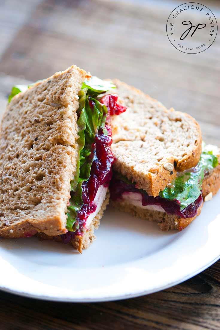 A delicious Leftover Turkey Sandwich sits on a plate, ready to sink your teeth into. There are layers of bread, turkey, cranberry sauce and lettuce visible.