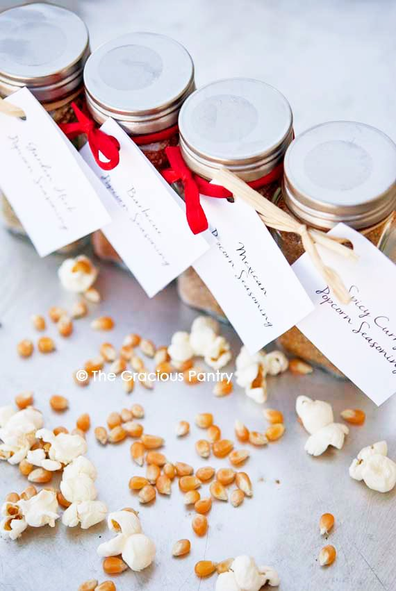 Four bottles of Clean Eating Popcorn Seasoning Recipes standing in a row with red bows tied around them showing that these make great personalized gifts for the holidays.