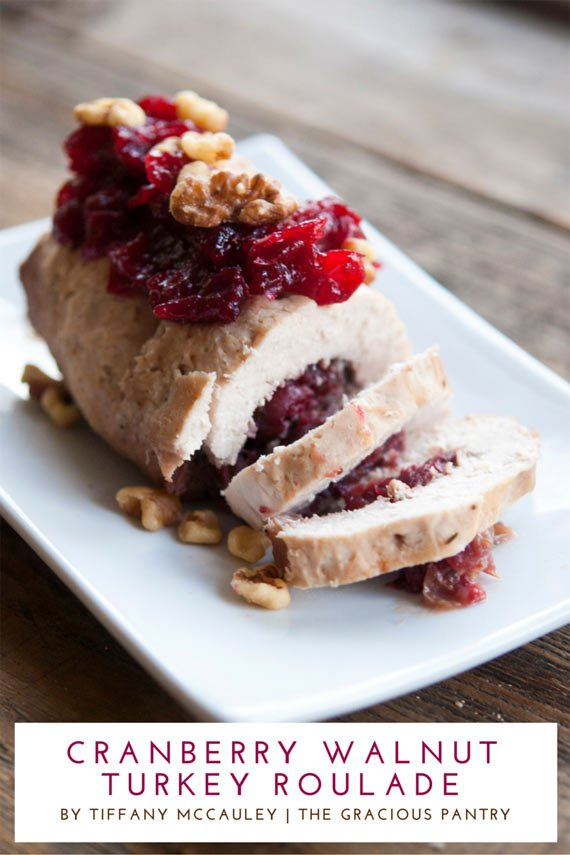 A Clean Eating Cranberry Walnut Pesto Roulade sits on a white serving platter with the first two slices laying cut in front of the roulade. You can see the cranberry sauce inside the turkey slices and there are walnuts sitting on top of the roulade for garnish.