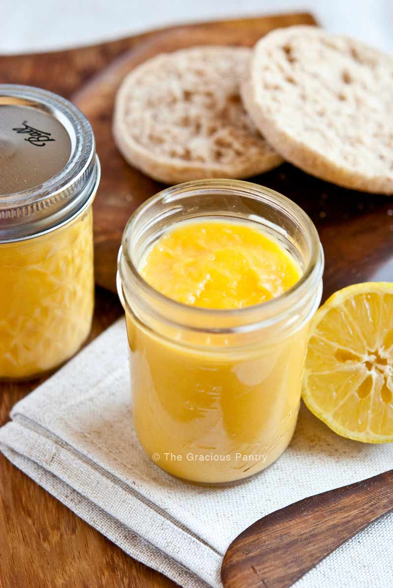 Two pint-sized canning jars containing Clean Eating Lemon Curd are surrounded by lemons and a whole grain english muffin. The lid of one of the jars is off so you can see the lemon curd inside.