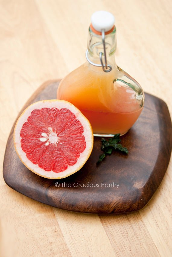 Clean Eating Grapefruit Vinaigrette Recipe shown in a dressing bottle sitting next to half a grapefruit. Both are sitting on a small, square, dark wood cutting board with rounded corners.