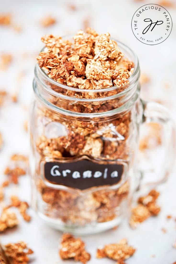 A mason jar sits filled to the rim with Clean Eating Maple Cinnamon Granola. There are small chunks of granola scattered around the base of the jar as well.