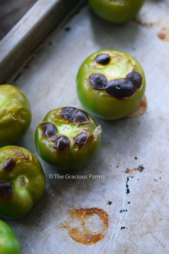 Several tomatillos on a baking sheet that have blistered tops from being roasted.