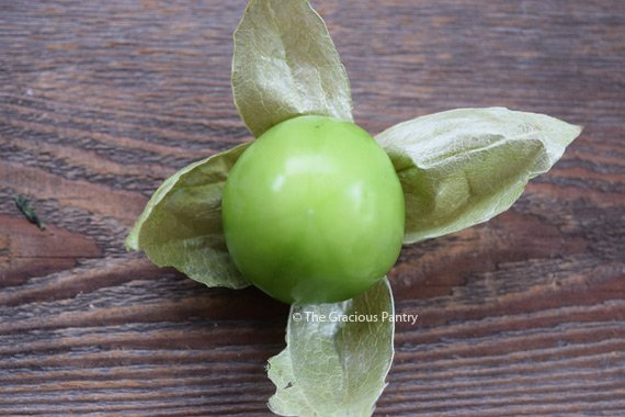 A single tomatillo with the husk pulled back looks like a star with the tomatillo still attached and sitting on top.