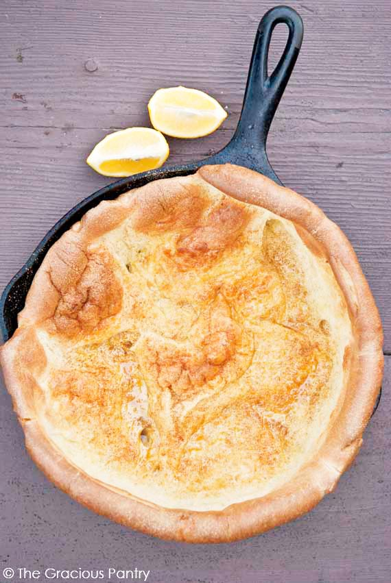 Clean Eating Dutch Baby Recipe shown from overhead looking down into the pan which is still in the skillet it was baked in. Two lemon wedges sit on the table just outside the black skillet. The dutch baby is golden brown and sprinkled with unprocessed sugar and lemon juice.