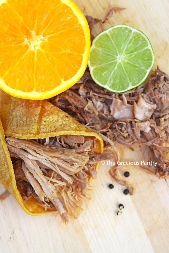 Clean Eating Slow Cooker Carnitas Recipe, shredded and displayed wrapped in a tortilla next to a halved orange and lime. Black peppercorns are roughly ground and sprinkled over the carnitas.