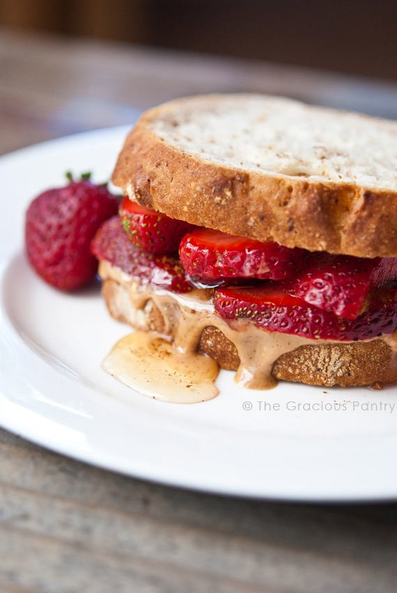 A Clean Eating Fruit And Nut Butter Sandwich sits on a white plate. You can see the sliced strawberries between the slices of bread and the honey and peanut butter oozing over the edge onto the plate just a tiny bit.